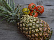 Fruit and vegetables - market natural supplies. Tomato and pineable over wood background Stock Photography