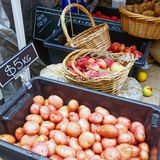 Fruit and Vegetables at Outdoor Market. Washed and freshly dug potatoes, and peaches and nectarines, in cane baskets, and pumpkins, at an outdoor fruit and Stock Images