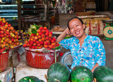 Fruit Vendor. An Asian woman sells fresh rambutans and melon fruit in the market in Vietnam Royalty Free Stock Photography