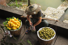 Fruit Vendor China. A chinese man wearing a traditional hat selling peaches and kiwis within Fenghuang village along side the Tuo jiang river stock images