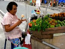 Fruit vendor selling green mangoes and cotton fruit at a sidewalk royalty free stock image