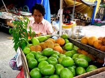 Fruit vendor selling green mangoes and cotton fruit at a sidewalk Stock Photos