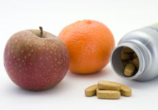 Fruit and vitamins. An apple, tangerine and a bottle of vitamin pills Stock Photo