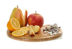 Fruit and vitamins in pills. Apple, pear, lemon and vitamins in pills Royalty Free Stock Photo