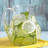 Fruit water in glass pitcher. Fruit water with lemon, lime, cucumber and mint in glass pitcher Stock Photo