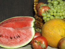 Fruit. Watermelon, melon, grapes and apples on the table. Red ripe juicy watermelon on the background of other fruits Royalty Free Stock Photos