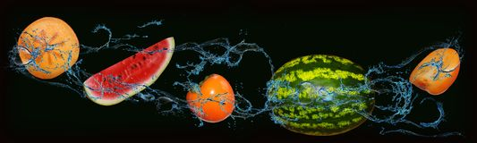 Fruit - watermelon, persimmon on an isolated black and green background stock photos