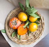 Fruit on a wicker plate. Persimmons and tangerines on a wicker plate Royalty Free Stock Images