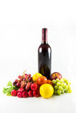 Fruit and wine. A photo of a bottle of red wine that has some kind of fruit around the bottom Royalty Free Stock Photos