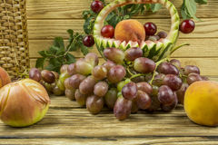 Fruit basket of watermelon, apples, peaches and grapes lying on. Fruit on a wooden background closeup royalty free stock photo