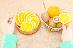 Fruit in a wooden bowl and basket, hands holdings on vessels Stock Photo