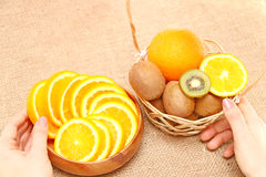 Fruit in a wooden bowl and basket, holding hands on vessels Stock Photo