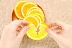 Fruit in a wooden bowl in his hand torn orange, ready for consum Stock Photo