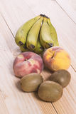 Fruit on wooden table. Bananas, peaches and kiwis. Fruit on wooden table. Bananas, peaches, kiwis and Paraguayans royalty free stock images