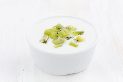 Fruit yogurt with kiwi in white bowl Stock Images