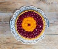 Fruitcake με τα κεράσια και tangerines στο αγροτικό ξύλο Στοκ εικόνες με δικαίωμα ελεύθερης χρήσης