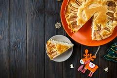 Fruitcake для рождества украшенный с яблоками на оранжевой плите на коричневом деревянном столе Печенье Delicioius домодельное Но стоковое изображение