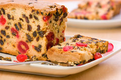 Fruitcake. Fresh fruitcake full of succulent cherries sultanas and raisins on white plate Stock Images