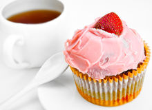 Fruitcake with a berry and a cup of tea Royalty Free Stock Image