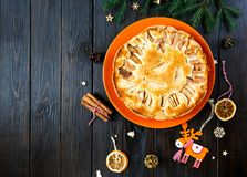 Fruitcake for Christmas decorated with apples on the orange plate on the brown wooden table. Delicioius Homemade Pastry. stock photos