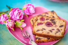Slices muffins with berry and dessert fork, bouquet of flowers on a wooden table. stock photography