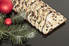 Fruitcake with marzipan. On black with bulbs and twigs Royalty Free Stock Photos
