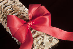 Fruitcake with marzipan. On black with red ribbon Stock Photo