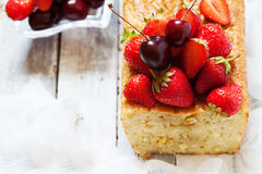 Fruitcake with strawberry and cherry topping Royalty Free Stock Image