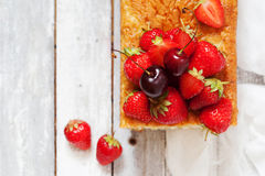 Fruitcake with strawberry and cherry topping Stock Photos