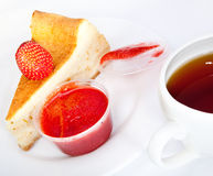 Fruitcake with a strawberry and  cup of tea Stock Photography