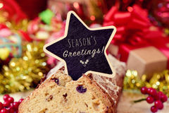 Fruitcake topped with a chalkboard with the text seasons greetin Stock Image
