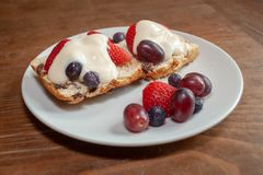 Scone with Fresh Fruit and Cream. Fruited scone and cream with strawberries, grapes and blueberries on a white plate on wooden table from side Stock Images