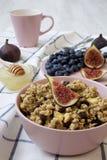 Fruitgranola met vruchten in een roze werpt klaar te eten, zijaanzicht close-up royalty-vrije stock afbeelding