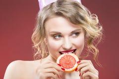 Fruitideeën Schuwe en Sexy Kaukasische Blonde Meisje het Bijten Grapefruit stock afbeelding