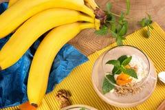 Fruitige smoothie in dessertglas met een tak van bananen op een gele en blauwe achtergrond Cocktails met droge abrikozen Royalty-vrije Stock Foto's