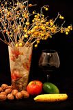 Fruitmengeling, glas wijn en vaas van bloemen op zwarte achtergrond Stock Afbeeldingen