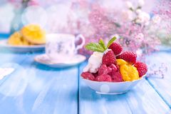 Fruitroomijs met frambozen en mango Bloemen en rijpe mango op een blauwe houten achtergrond Het ontbijt is zoet en koffie stock fotografie