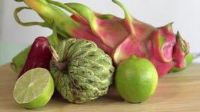 Fruitrotatie op houten achtergrond Sluit omhoog lengte van exotisch fruit: Gehalveerde hartstocht, draak, annona, vlaappel, guave stock videobeelden