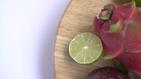 Fruitrotatie op houten achtergrond Sluit omhoog lengte van exotisch fruit: Gehalveerde hartstocht, draak, annona, vlaappel, guave stock video