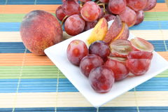 Fruits. Table with fruits - peach and pink grapes Royalty Free Stock Photo