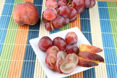 Fruits. Table with fruits - peach and pink grapes Royalty Free Stock Image