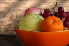 Fruits. Mixed fruits in an orange plastic bowl on a pantry in kitchen Royalty Free Stock Image