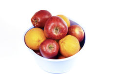 Fruits. Apples and oranges in a fruit bucket in front of white background Stock Photo