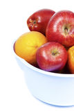 Fruits. Apples and oranges in a fruit bucket in front of white background Stock Photos