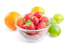 Fruits. Glass bowl filled with fresh ripe strawberries arranged with some citrus fruits oranges and limes around isolated on white background stock photo