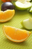 Fruits. Some fruits such as sliced orange and apple and a plum, on an green woven background Stock Photos