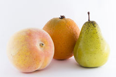 Fruits. A peach, an orange and a pear in a  with white background Royalty Free Stock Images