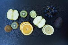 Fruits. Apple, kiwi, orange, avocado, grapes and lime on dark background Royalty Free Stock Image