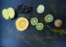 Fruits. Apple, kiwi, orange, lime and grapes on dark background Royalty Free Stock Images
