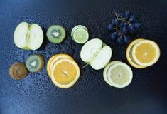 Fruits. Apple, kiwi, orange, lime, lemon and grapes on dark background Stock Photos